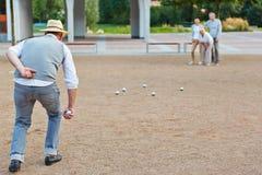 Groupe supérieur jouant le boule dans une ville Images stock
