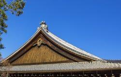 Groupe sur le toit japonais de temple contre le ciel bleu Photographie stock
