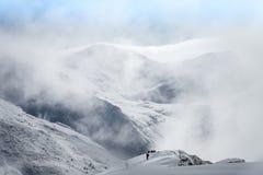 Groupe trimardant sur les montagnes couvertes de neige en hiver Photos stock