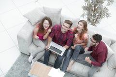 Groupe triomphant d'amis riant tout en se reposant sur le divan dans le salon Photographie stock
