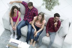 Groupe triomphant d'amis riant tout en se reposant sur le divan dans le salon Image libre de droits