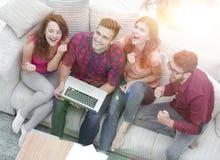 Groupe triomphant d'amis riant tout en se reposant sur le divan dans le salon Photo libre de droits