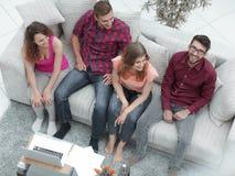 Groupe triomphant d'amis riant tout en se reposant sur le divan dans le salon Images stock