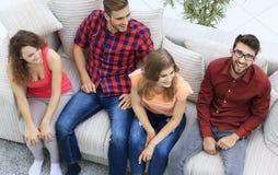 Groupe triomphant d'amis riant tout en se reposant sur le divan dans le salon Images libres de droits