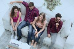 Groupe triomphant d'amis riant tout en se reposant sur le divan dans le salon Photo stock