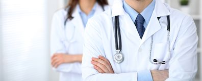 Groupe of unknown doctors standing straight in hospital office. Close Up of stethoscope at practitioner breast.  royalty free stock photography