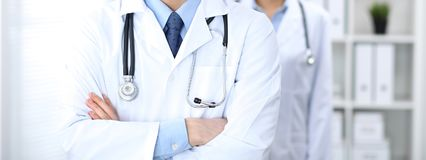 Groupe of unknown doctors standing straight in hospital office. Close Up of stethoscope at practitioner breast.  stock photo