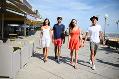 Groupe of young people man and woman walking on seaside of touristic resort during sunny summer day. Groupe of young people men and women walking on seaside of royalty free stock images