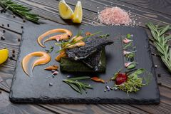 Grouper`s grilled fillet on a spinach bed. Fish on the black slate, shale board. Lemon pieces, sauce and rosemary. Piece of fish on wooden table Royalty Free Stock Photo