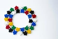 Groupes de meeples colorés en cercle d'isolement sur le fond gris Cadre rond coloré des composants de jeu Petites figures de l'ho images stock