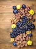Groupes de raisins et de figues mûrs frais sur un beau fond de fond en bois avec une branche des raisins bleus et rouges Figues v Image stock