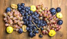 Groupes de raisins et de figues mûrs frais sur un beau fond de fond en bois avec une branche des raisins bleus et rouges Figues v Photos stock