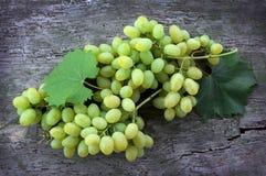 Groupes de raisins mûrs verts sur le fond en bois Photo stock