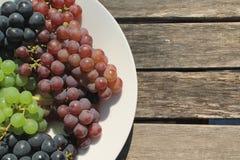 Groupes de raisins mûrs sur une table en bois ensoleillée Photos libres de droits