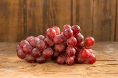 Groupes de raisins rouges mûrs frais sur une table en bois Photographie stock libre de droits