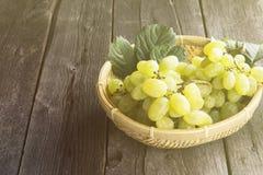 Groupes de raisins verts dans la cuvette wattled sur un backgr en bois foncé Photo stock