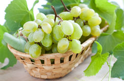 Groupes de raisins verts dans un panier en osier Photos stock