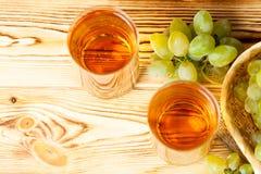 Groupes de raisins verts mûrs frais dans le panier en osier sur le morceau de toile à sac et deux verres avec le jus de raisins s Photos stock