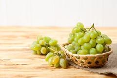 Groupes de raisins verts mûrs frais dans le panier en osier sur le morceau de toile à sac sur un contexte texturisé en bois Beau  Photo libre de droits