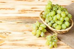Groupes de raisins verts mûrs frais dans le panier en osier sur le morceau de toile à sac sur un contexte texturisé en bois Beau  Photos stock