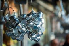 Groupes de tasses brillantes de boissons en métal accrochant devant un vieux magasin traditionnel près du bazar grand Photos libres de droits