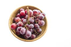 Groupes juteux d'isolement de grands raisins rouges dans une cuvette en bois photographie stock libre de droits