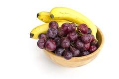 Groupes juteux d'isolement de grands raisins rouges et de bananes mûres dans une cuvette en bois images stock