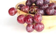 Groupes juteux d'isolement de grands raisins rouges lovés d'une cuvette en bois image libre de droits