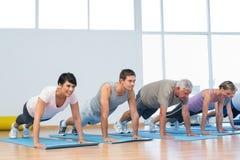 Groupez faire des pousées dans la rangée à la classe de yoga Image stock