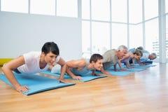 Groupez faire des pousées dans la rangée à la classe de yoga Photo stock