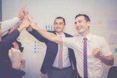 Groupez l'équipe asiatique de personnes d'affaires avec le geste de succès donnant salut cinq lors de la réunion, accord photo libre de droits