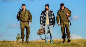 Groupez le ciel bleu de fond de nature de chasseurs ou de garde-chasse d'hommes Types recueillis pour la chasse Les hommes porten images libres de droits