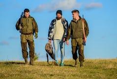 Groupez le ciel bleu de fond de nature de chasseurs ou de garde-chasse d'hommes Types recueillis pour la chasse Les hommes porten photos stock
