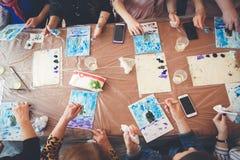 Groupez le dessin avec des peintures se reposant à la table photo stock