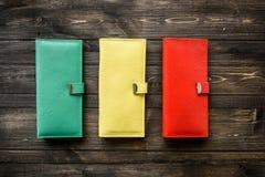Groupez le portefeuille coloré de peau en cuir sur le fond en bois Photo libre de droits