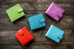 Groupez le portefeuille coloré de peau en cuir sur le fond en bois Image stock