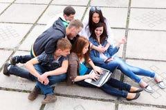 Groupez les étudiants s'asseyant avec un ordinateur portatif sur le stree Photos libres de droits