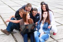 Groupez les étudiants s'asseyant avec un ordinateur portatif sur le stree Photographie stock libre de droits