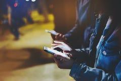 Groupez les amis adultes de hippies employant dans des mains téléphone portable moderne, concept en ligne d'Internet de Wi-Fi de  image stock