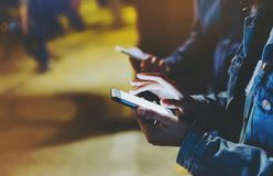 Groupez les amis adultes de hippies employant dans des mains téléphone portable moderne, concept en ligne d'Internet de Wi-Fi de  Images libres de droits