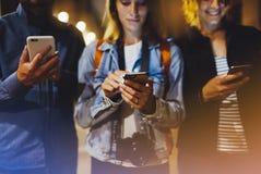 Groupez les amis adultes de hippies employant en plan rapproché de téléphone portable de mains, concept en ligne d'Internet de Wi Photographie stock