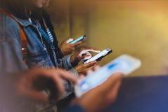 Groupez les amis adultes de hippies employant en plan rapproché de téléphone portable de mains, concept en ligne d'Internet de Wi photo stock