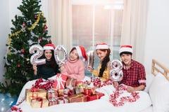 Groupez les amis célébrant Noël à la maison et montrant 2018  Photo libre de droits