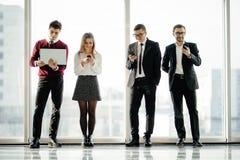 Groupez les amis d'affaires tenant et à l'aide des instruments modernes sur le fond de fenêtres Concept de travail d'équipe d'ami Image libre de droits