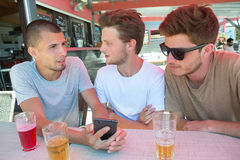 Groupez les amis heureux avec des smartphones et les boissons à la barre Photos libres de droits