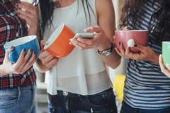 Groupez les beaux jeunes appréciant en conversation et café potable, filles de meilleurs amis ayant ensemble l'amusement, posant  Photo stock
