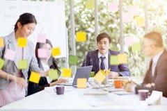 Groupez les gens d'affaires asiatiques avec le fonctionnement et le brainst occasionnels de costume Image stock