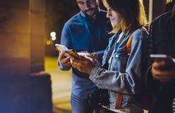 Groupez les hippies adultes employant en plan rapproché de téléphone portable de mains, concept en ligne d'Internet de Wi-Fi de r photos libres de droits