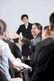 Groupez les hommes d'affaires, orientation sur le femme dans l'assistance Images libres de droits