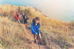 Groupez les jeunes femmes des randonneurs marchant avec le sac à dos sur une montagne au coucher du soleil Camper allant de voyag photo libre de droits